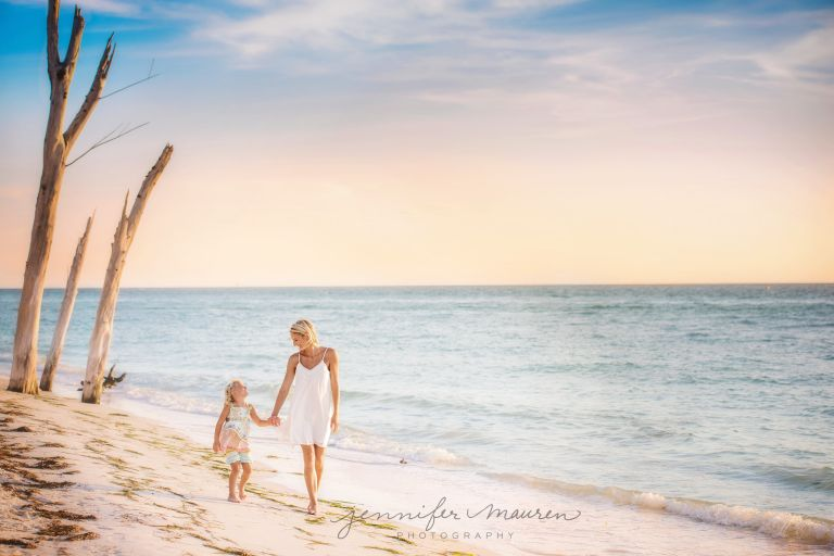 mom and daughter walking beach