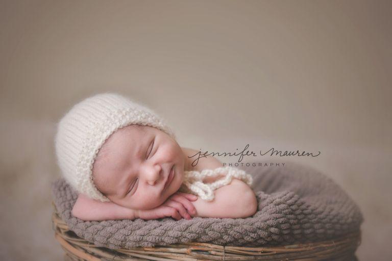 Newborn baby boy in basket with bonnet