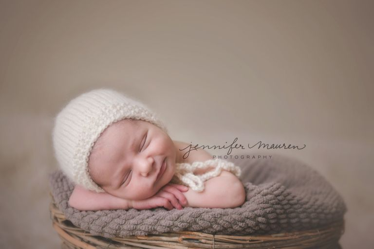 Newborn baby boy in basket with bonnet